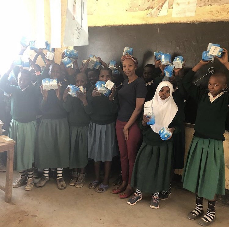 Several girls standing in front of a blackboard in a Tanzanian classroom, holding packets of sanitary towels.