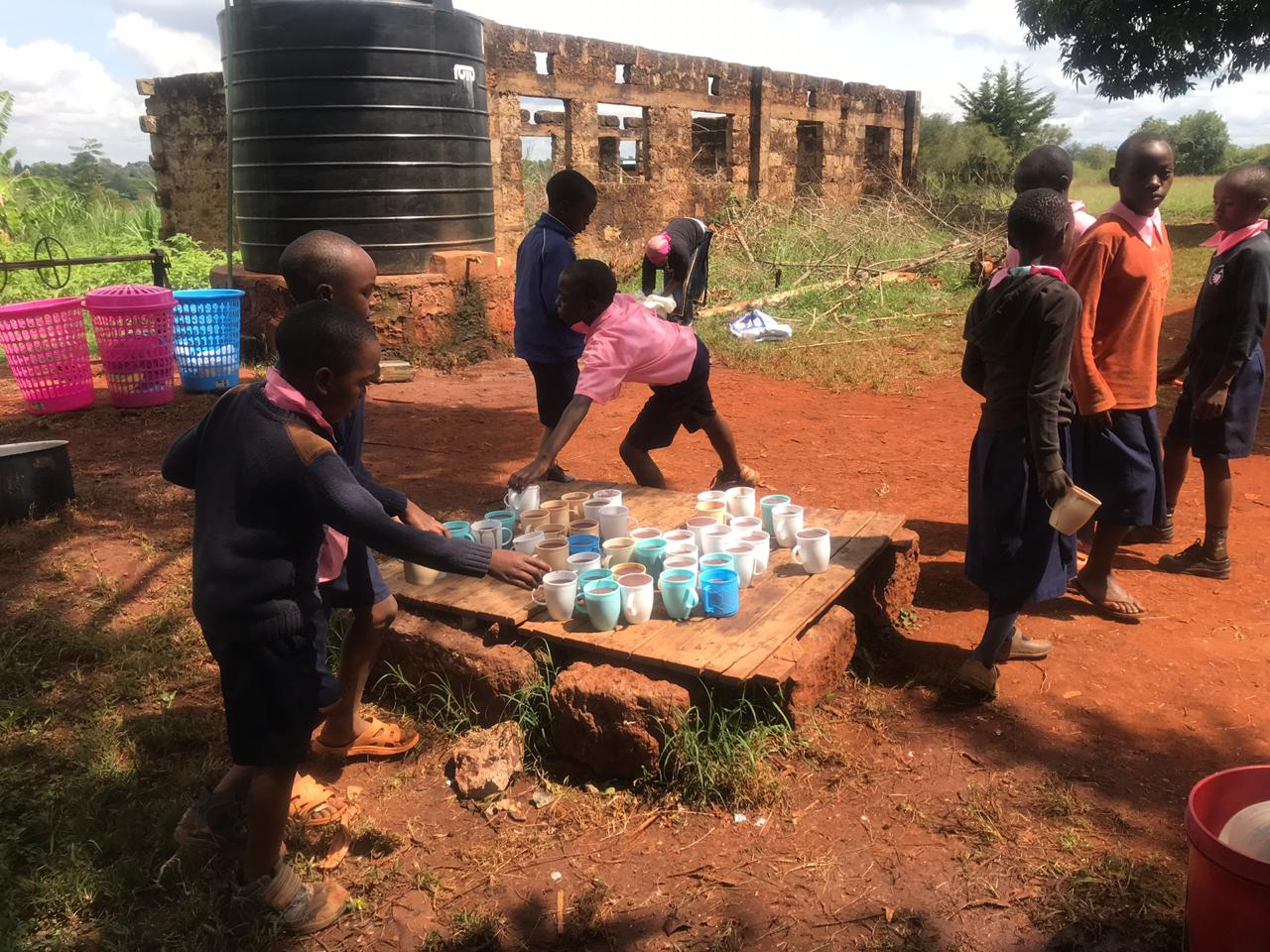 Children collecting mugs of porridge at Mwtingiri Primary School, Kenya
