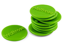 A pile of green Waitrose community matters tokens against a white background, with a single token beside the pile.