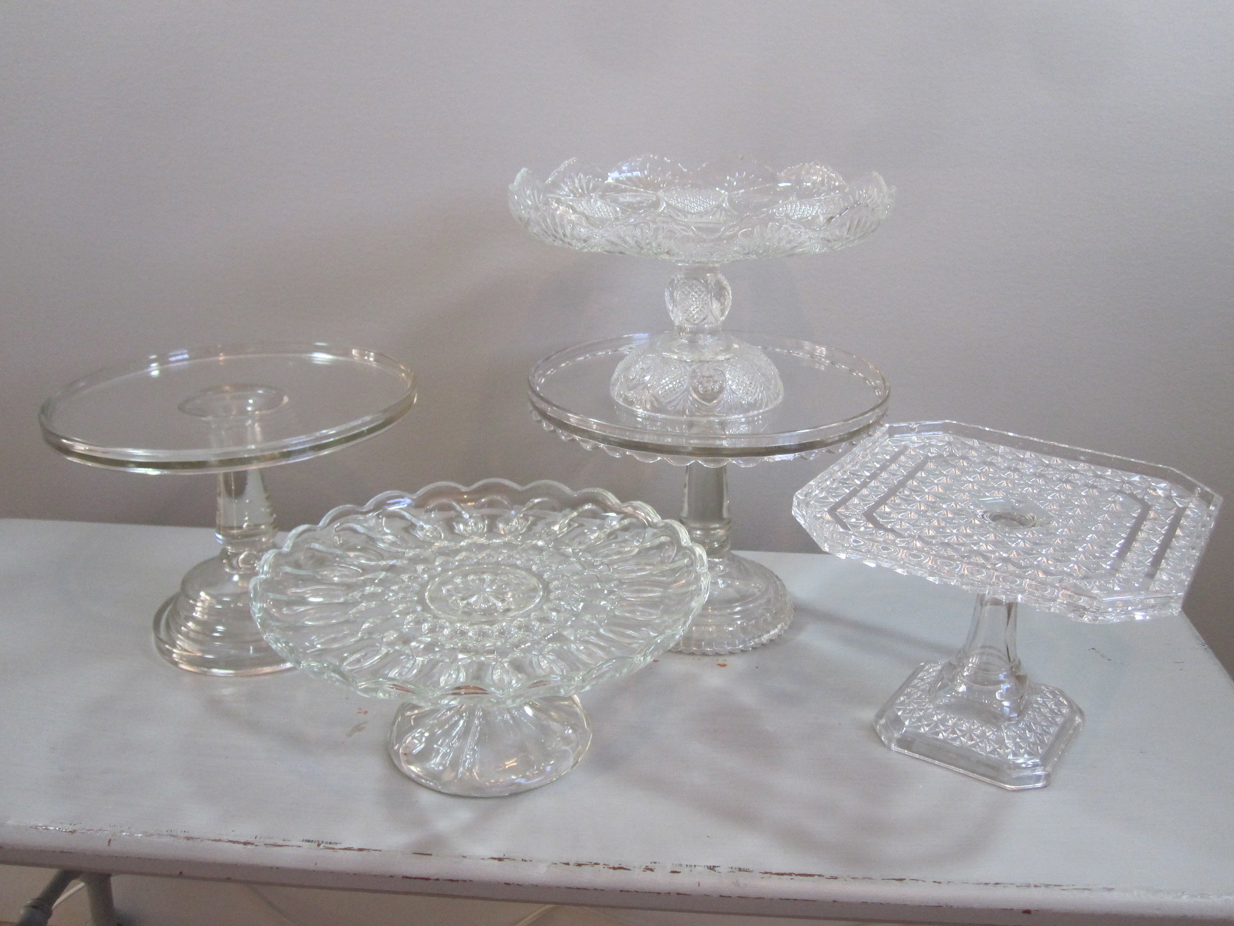 Pedestal Cake Plates - Description ~ assorted shapes, height & sizes; great to stack and display cupcakes, cookies & moreQuantity ~ 20Rental Price ~ $8