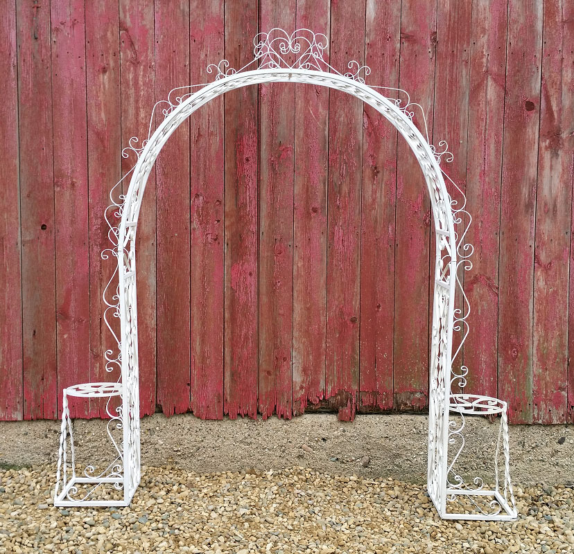 Iron Arch - Description ~ vintage style arch with plenty of curly fancy metal pieces; can be decorated with flowers or fabric or use as is. Seats on the side can hold flowersQuantity ~ 1Price ~ $45