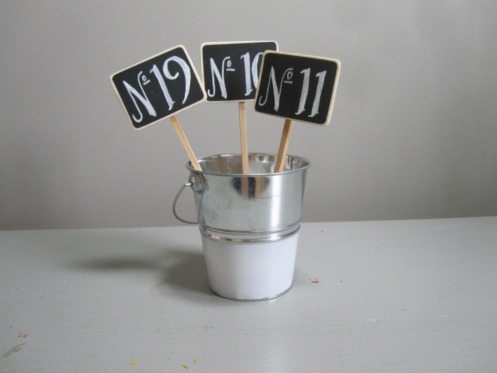Chalkboard Table # - Description ~ small chalkboard numbers on stakes that can be placed in centerpieces, jars or other containersQuantity ~ 30Price ~ $.50