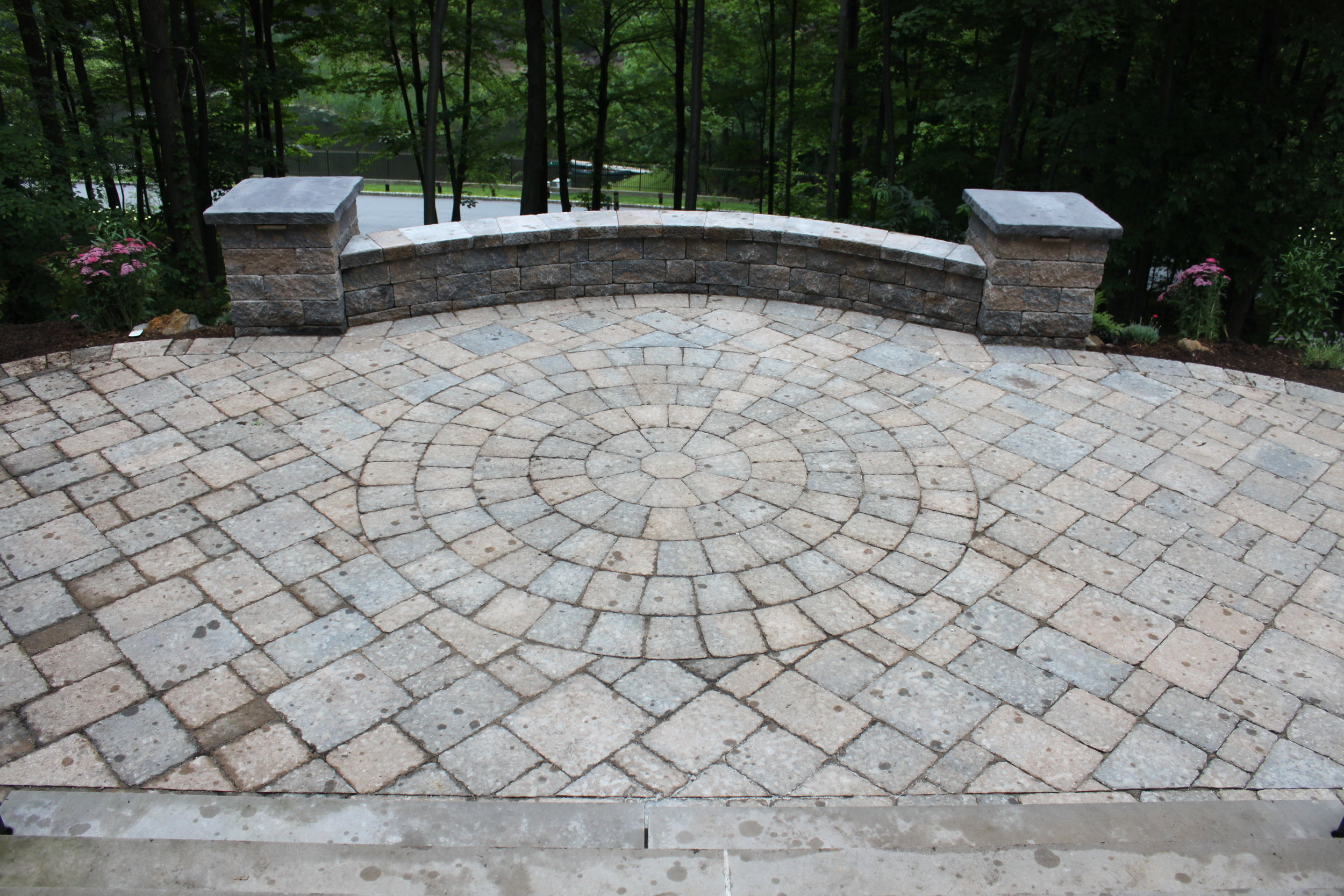 A view of a paver stone walkway from the front steps of a home. The walkway has a circular pattern in the center, and has a low wall on one side.