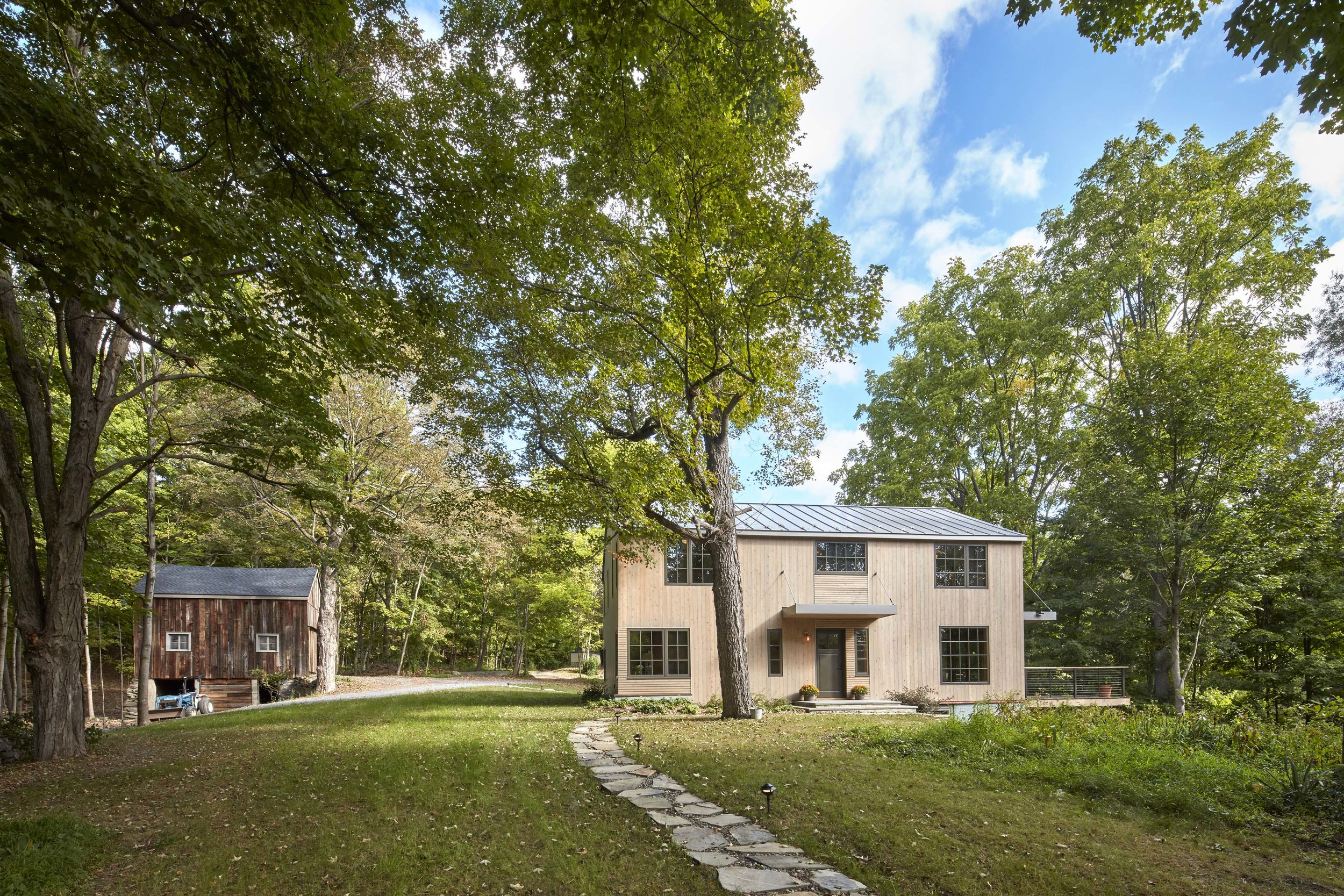 Fallkill Farm - Year: 2016Type: ResidentialLocation: Hyde Park, NYSquare Footage: 2,350Scope of Work: Architectural and Interior DesignAwards: New York Cottages and Gardens2017 Innovation in Design Award Winner,Architecture CategoryAn existing 1830's farmhouse located in historic Hyde Park, NY underwent a full-gut renovation to transform into a Rustic Modern retreat. A speculative project in collaboration with custom-home builder, Wolcott Builders, the two-story house sits on 36 acres and is surrounded by three large barns and a pond.The main goal of the project was to retain the house's historical elements such as exposed timber members and a stone hearth, which was built by the original owner with help from his children. In order to do so, we added modern details and amenities, incorporated purposeful elements and provided outdoor views of the beautiful property while maintaining the farmhouse vernacular. The result is a historic yet modern home that complements the surrounding structures.