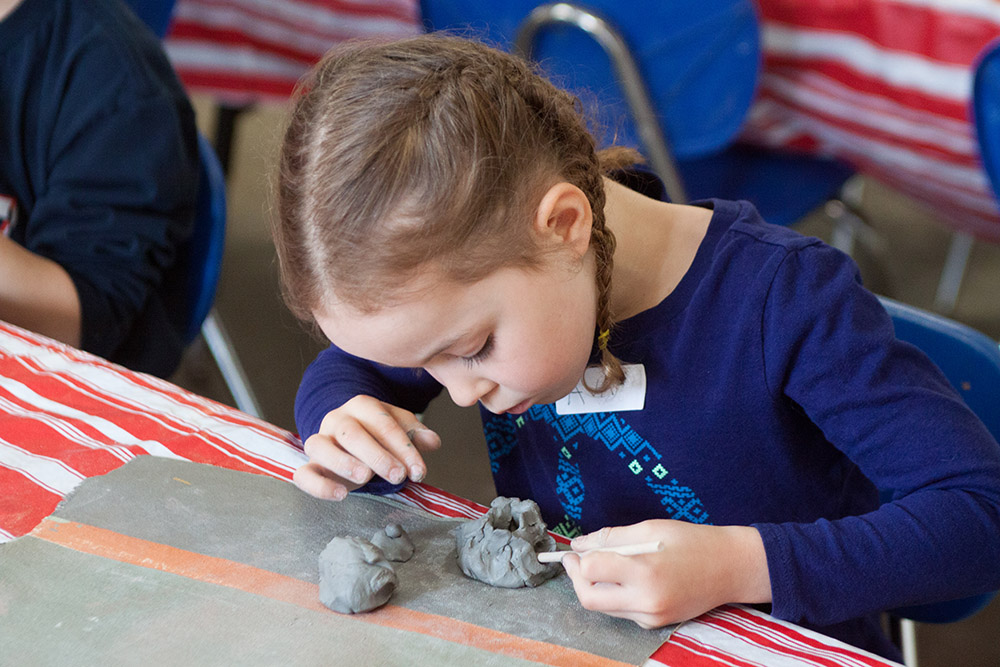 Grades K-8th engage in a full ceramics program that includes glazing and firing clay sculptures.