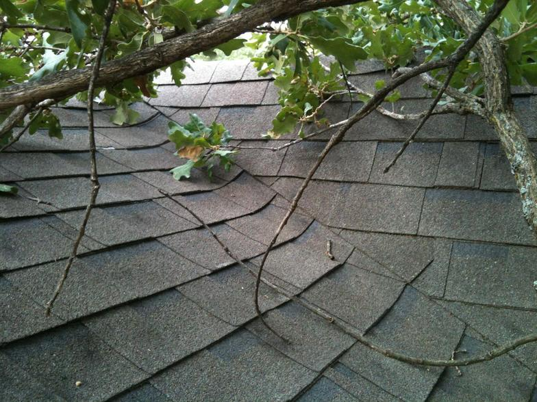 A residential shingle roof hit by tree debris after a storm.