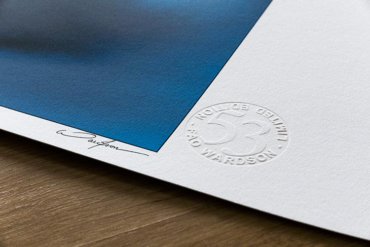 Détail de la signature imprimée et du timbre sec en périphérie de la surface encrée.