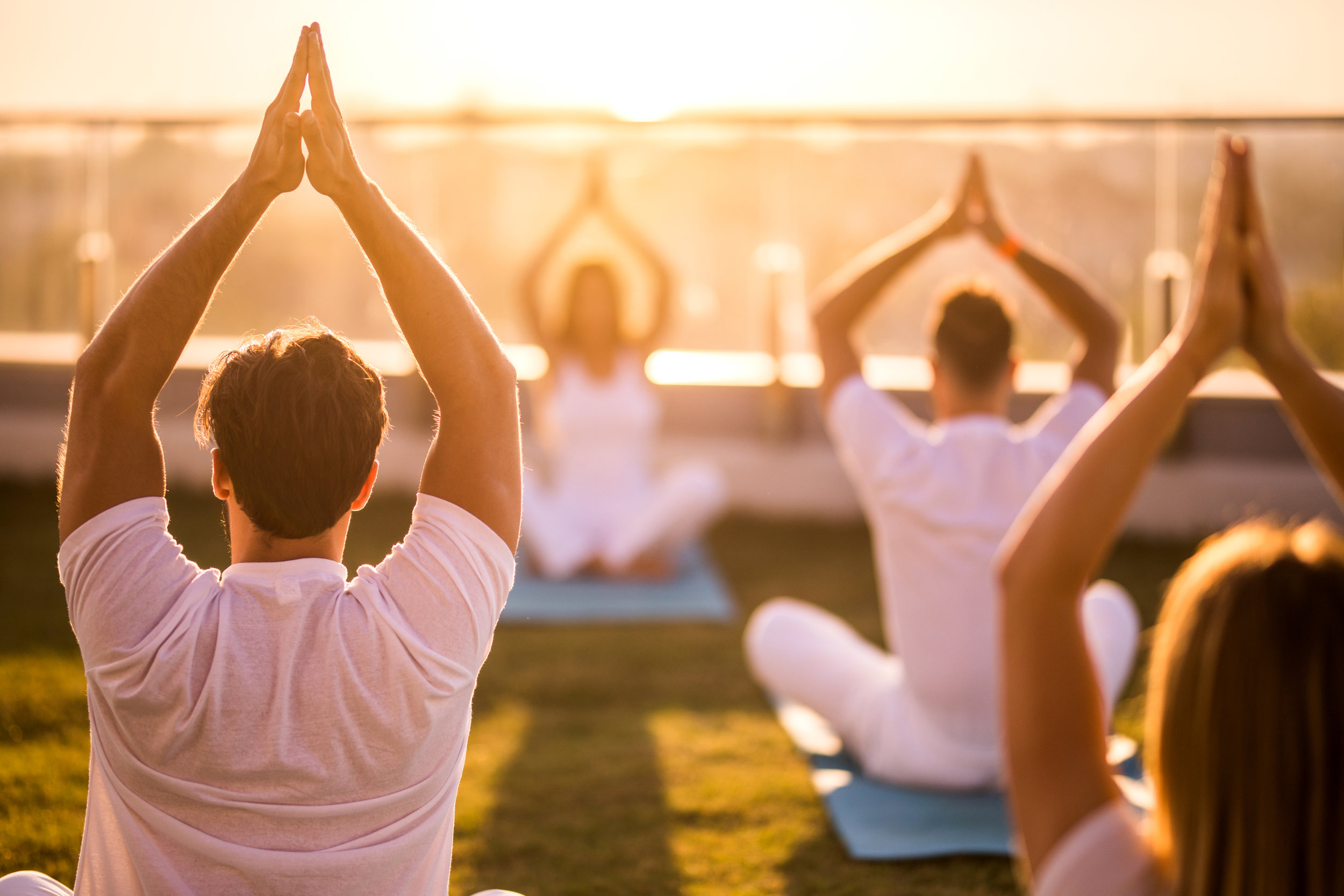 Rear-view-of-group-of-people-doing-Yoga-meditation-exercises-on-a-terrace.-888019184_6720x4480 (1).jpeg