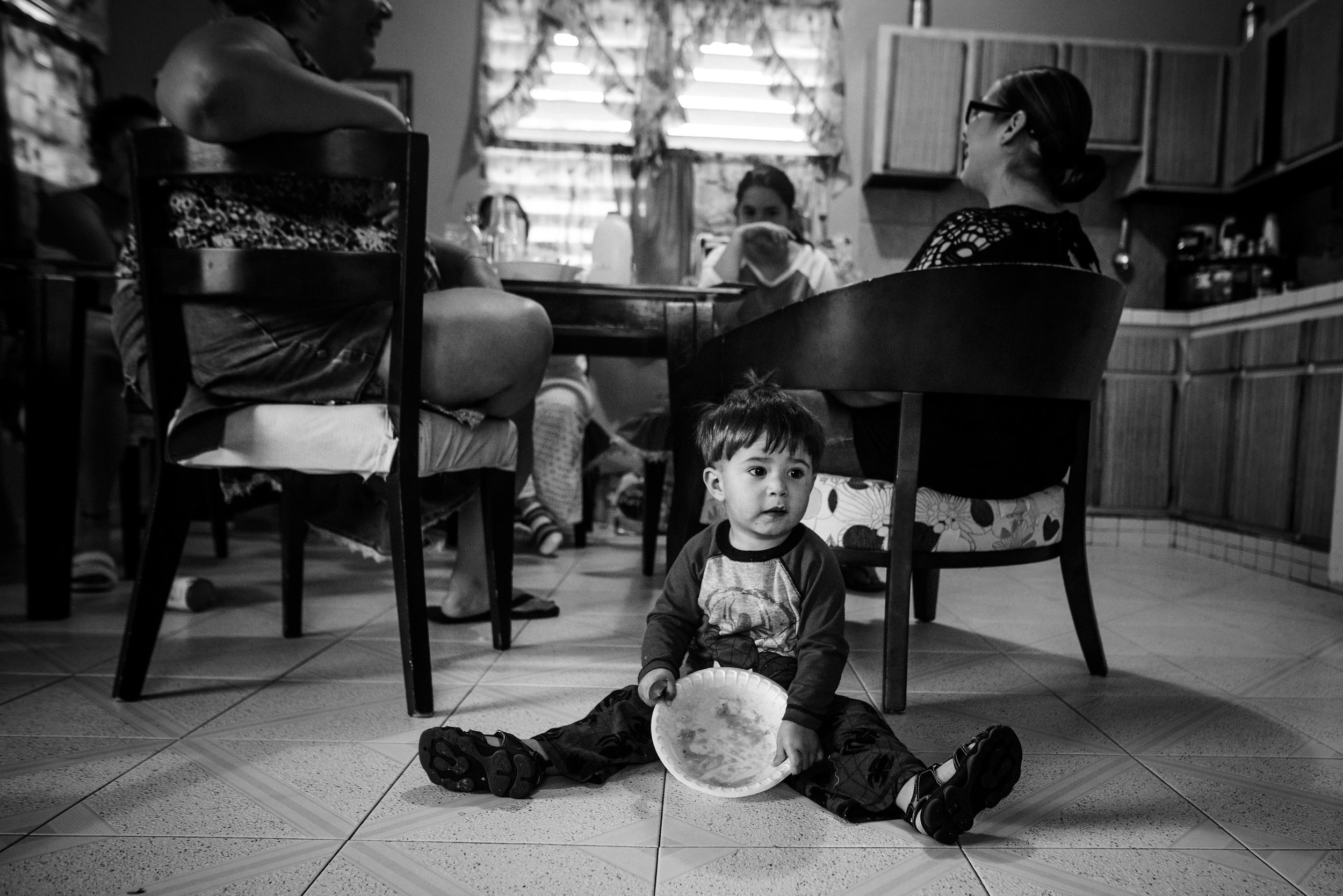 Photo credit: Aniya Emtage Legnaro  Grise (far right) sits at the table with her mother and sister while her nephew finishes breakfast from a paper plate. At the time this was photographed, there was no running water and so eating from disposable utensils saved the purchased water. Orocovis, Puerto Rico