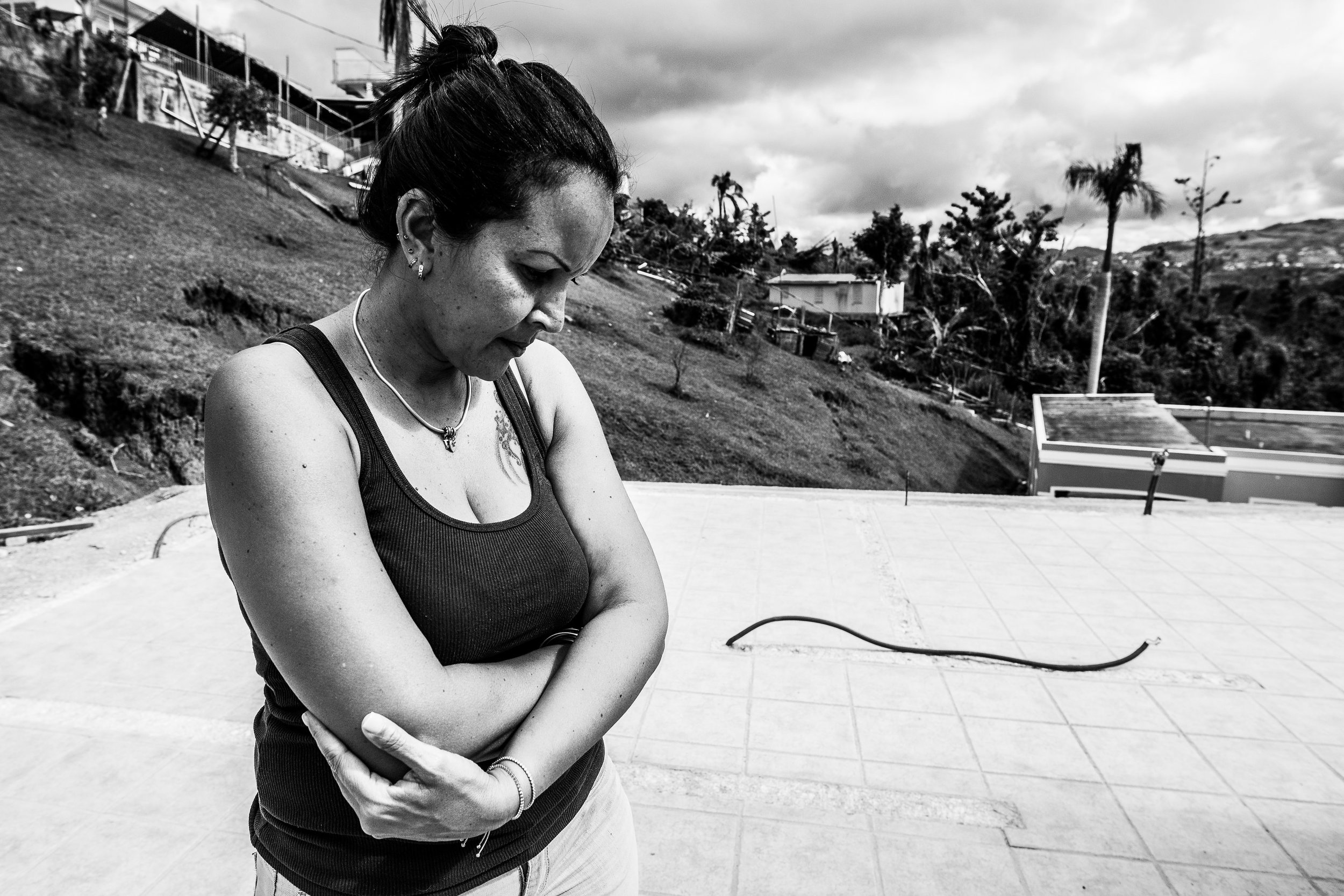 Photo credit: Katie Jett Walls  Denisse stands on the clean white tile floor of her home. No roof, and the only remaining walls are a cinderblock cubicle where the bathroom was. As her family weathered Hurricane Maria in the nearby home of her in-laws, Denisse's children watched their house lift off its foundation and plunge into the valley. Denisse ran a business from her house, so the equipment and supplies for her livelihood were lost with the house. The family is somewhat fortunate in that FEMA aid totals about $10,000. But, the estimate costs of rebuilding the home to be around $35,000. More troubling for the moment, though, is the fact that they ordered cinderblocks to begin rebuilding, and paid, in mid-November. The cinderblocks have yet to arrive, and they don't know when they will. It is Denise's understanding that FEMA has legal right to take any supplies that arrive in port, and she thinks maybe FEMA used their cinderblocks for something. Meanwhile, the price of basic building supplies has more than doubled on the island. She thinks maybe US suppliers (thanks to the Jones Act, all shipments of anything to Puerto Rico have to come from US suppliers in US ships) are hiking up prices of supplies to Puerto Rico.  UPDATE: in mid-February, 2018, the cinderblocks arrived. They came just a few days after electricity was restored on Denisse's entire street.