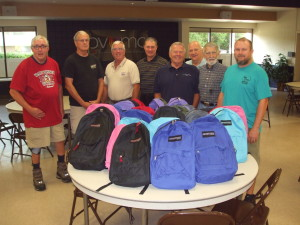 United Methodist Men stand behind the backpacks they assembled for the Methodist Home for Children