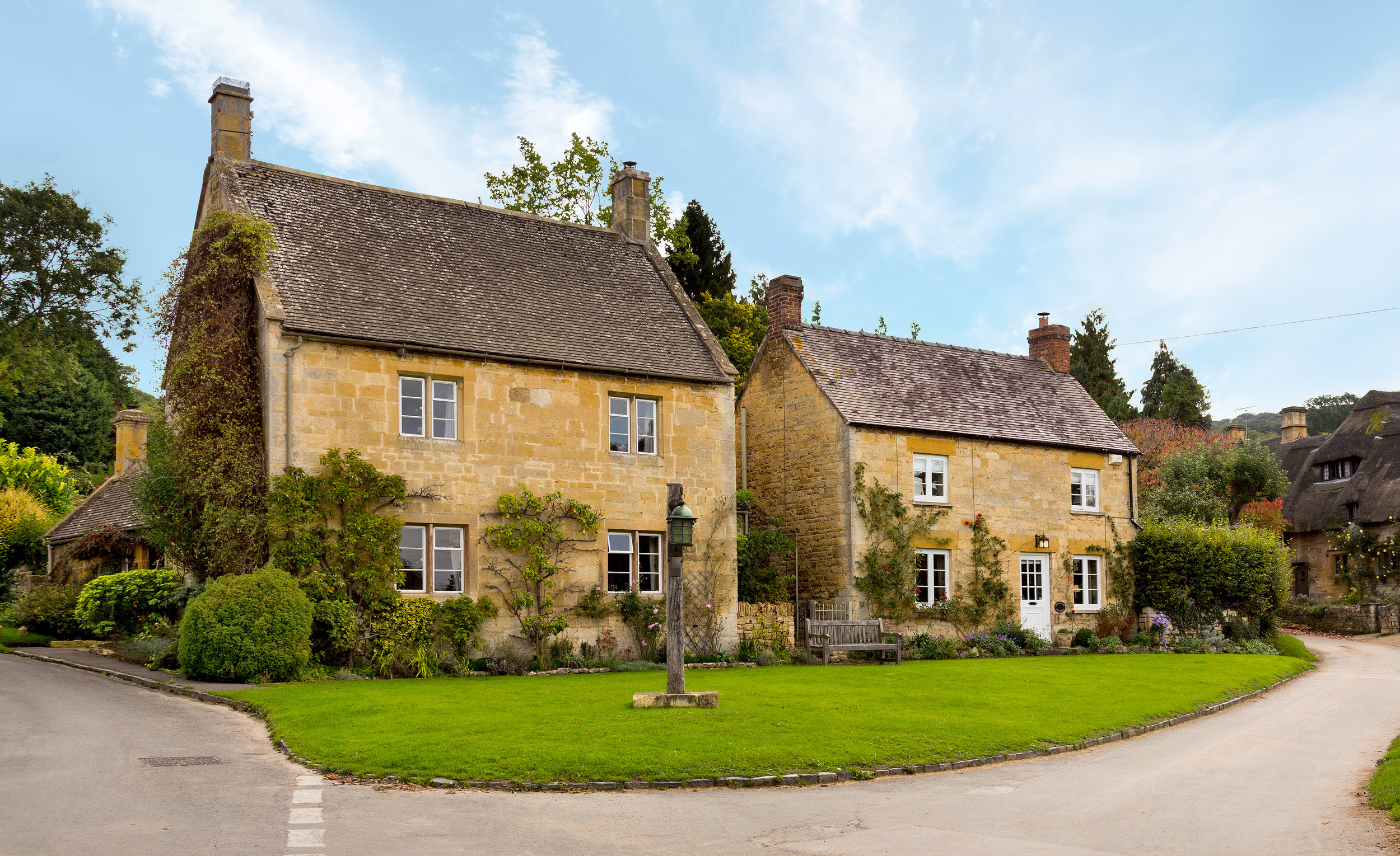 Beautiful sandstone village country cottages on road blue sky retouching