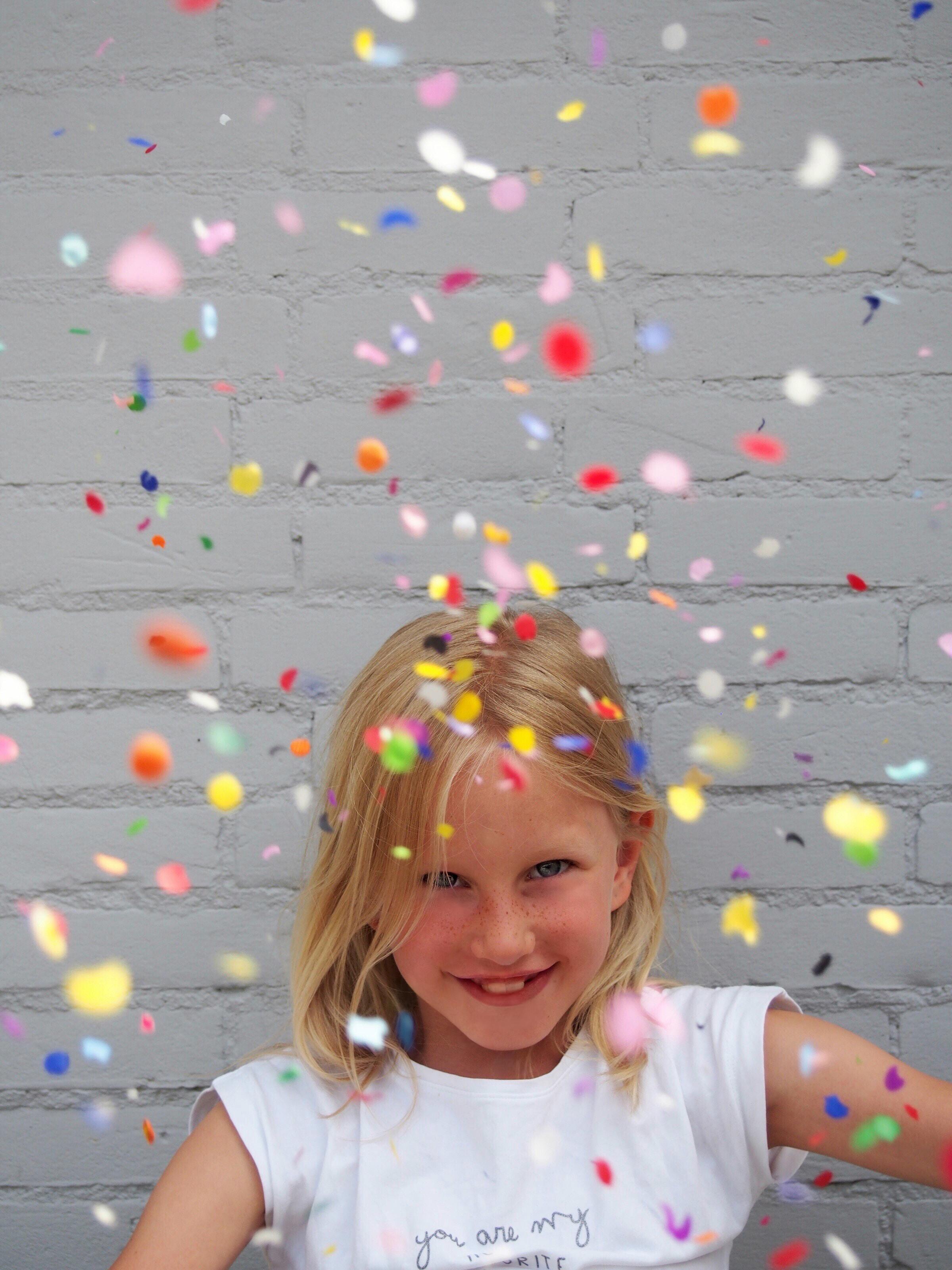 Happy girl portrait with confetti retouching
