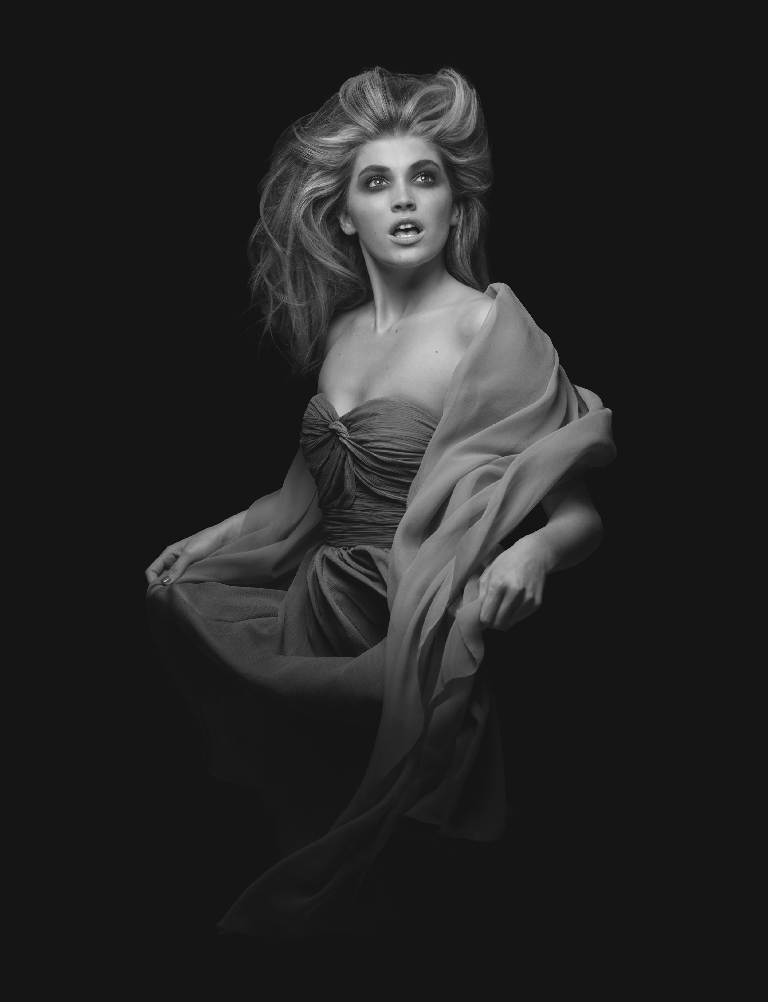 Female model with cosmetic makeup, wind blown hair, gown and shawl black and white studio fashion portrait retouching