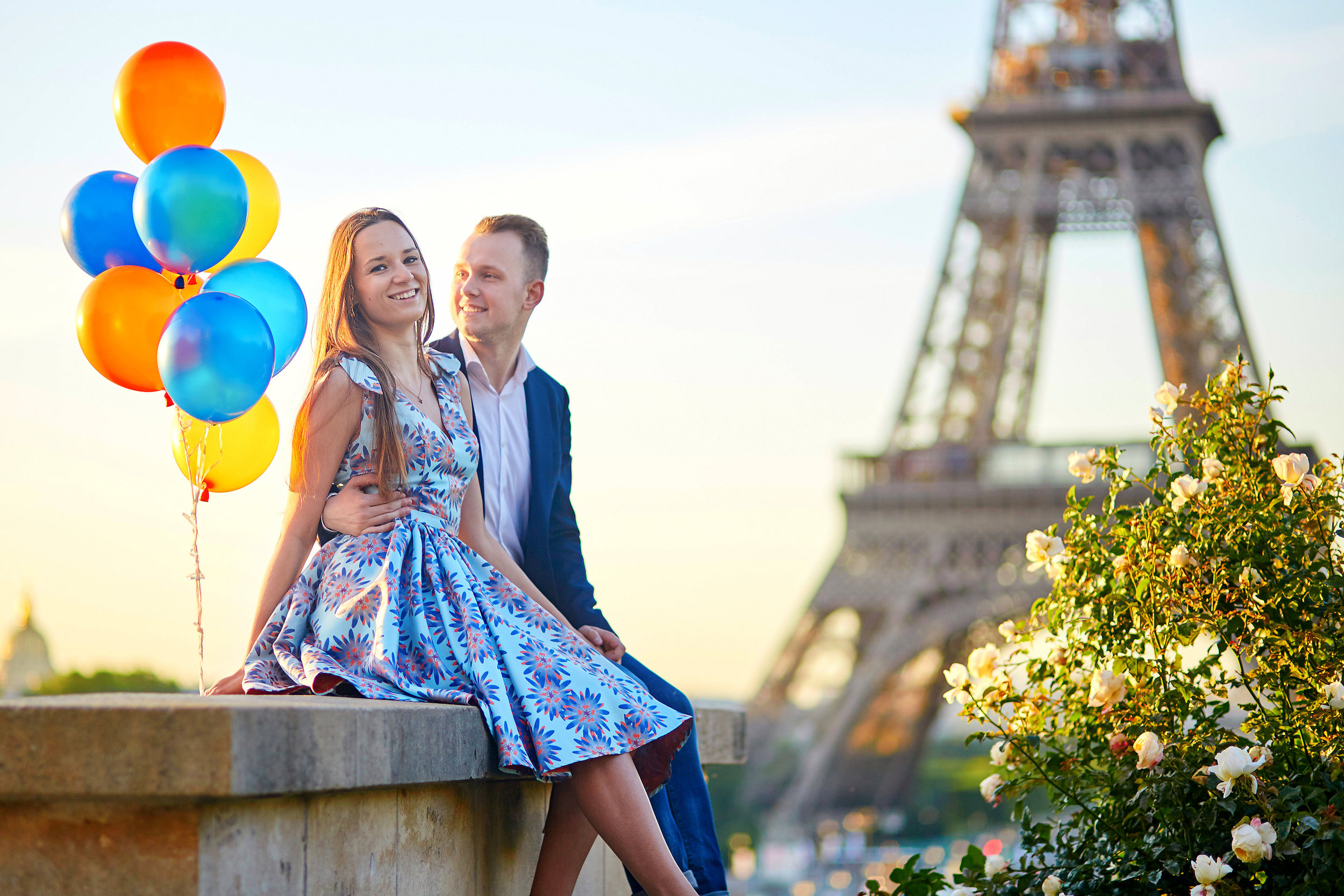 Happy young couple portrait by Eiffel Tower Paris and balloons