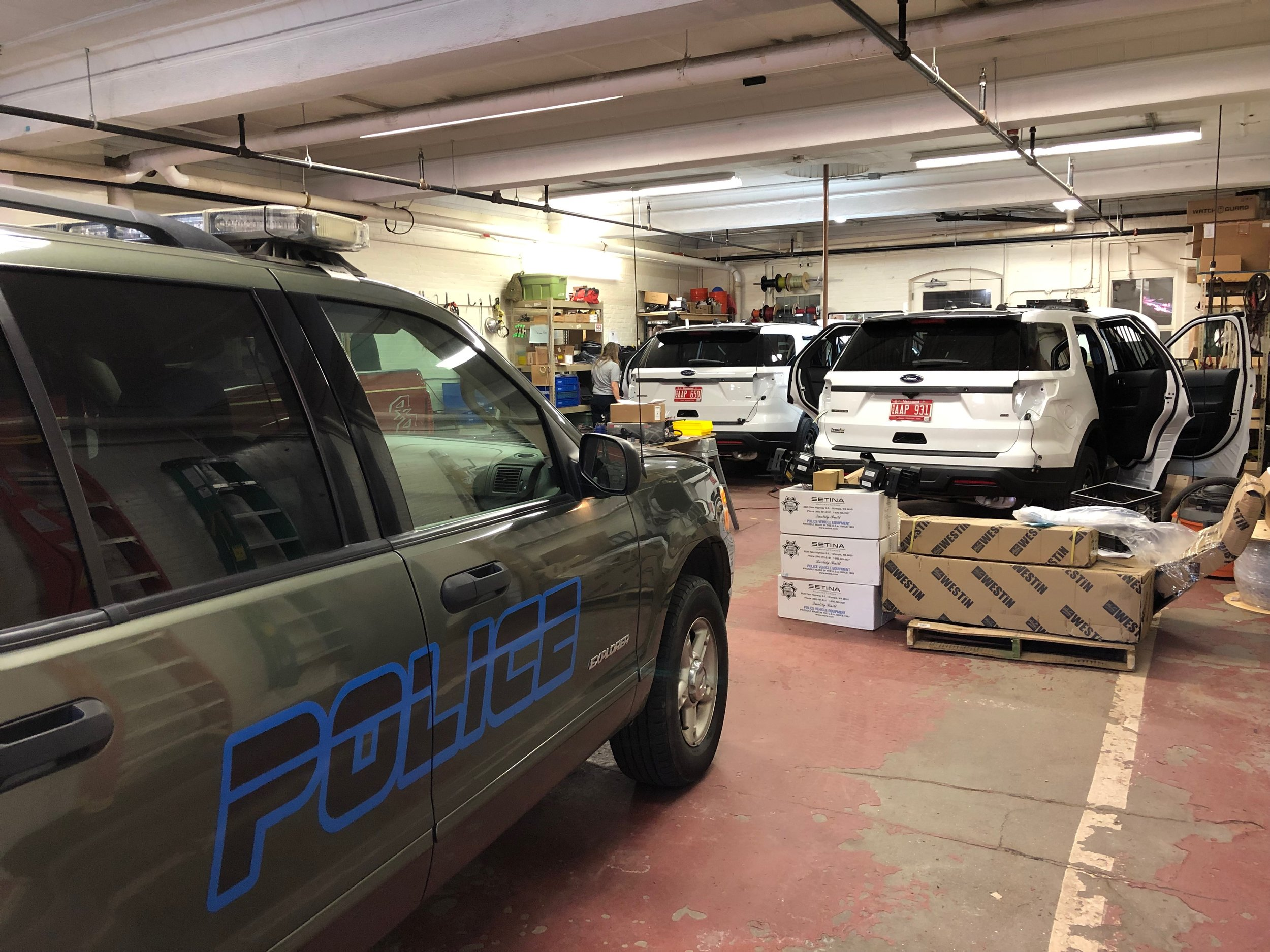 """Our Upfitting Division is busy. The 2 white cruisers in front are new for Brattleboro PD. They are getting a """"soup to nuts"""" complete upfitting. The gray cruiser is from Roxbury PD and is getting all equipment removed to be placed into a newer cruiser.  For all your needs contact Tom Powers at 603-355-2315 or at tpowers@firemutualaid.com"""