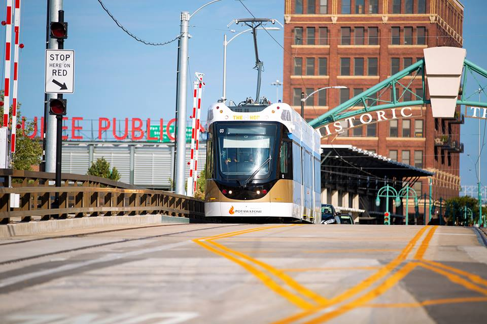 Milwaukee Streetcar (The Hop) traveling down a street in Milwaukee with the Milwaukee Public Market in the background.