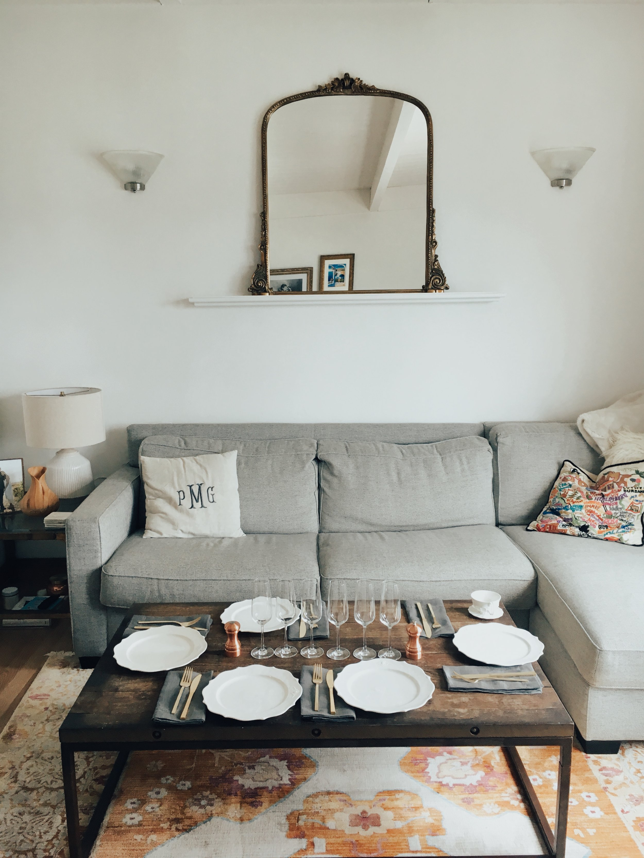 Pictured:  gold mirror ,  table lamp ,  patterned rug ,  champagne flutes ,  white plates ,  matching tea cups ,  gold flatware ,  copper salt & pepper mills ,  linen napkins ,  faux fur throw