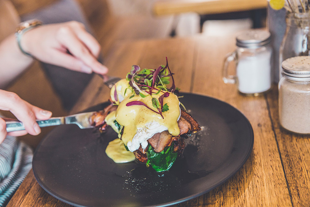 Delicious Eggs Benedict over bacon and fresh garnishes.