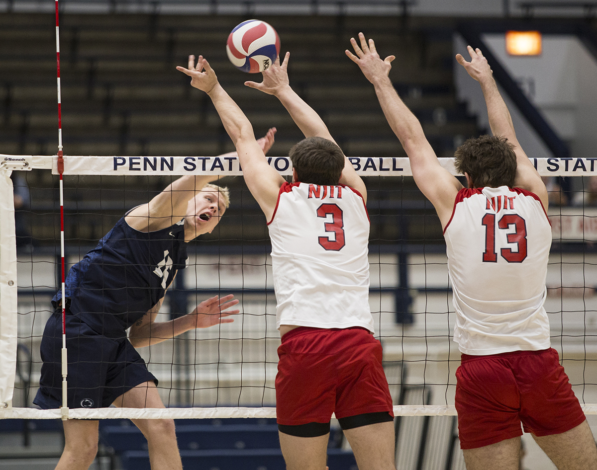 Opposite hitter Aidan Albrecht (15) spikes the ball over the heads of Bailey Mundy (3) and Luca Berger (13) during the Penn State v. New Jersey Institute of Technology in Rec Hall on Saturday, April 14, 2018. Penn State defeated New Jersey Institute of Technology 3-1.