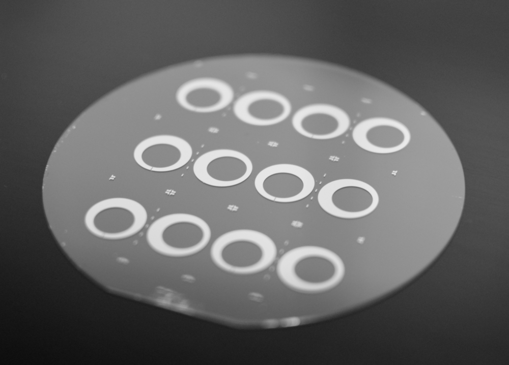 Optical image  of a wafer patterned with several 2.5D cQED chip-stack layers, before dicing. The wafer is diced into chips, which are stacked on top of each other, see next figure.Sample pattern, both large and fine structures, were defined with a 100 kV electron-beam pattern generator ( Raith EBPG 5000+ ) in a single step on a PMAA/MAA resist bilayer.