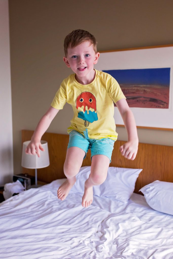 child bouncing on a bed