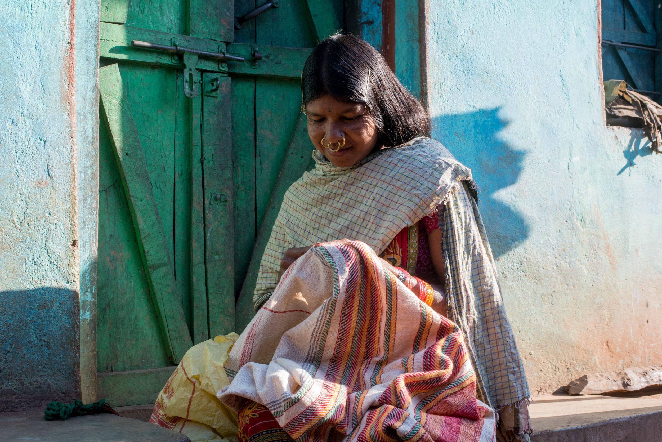 Dongria girl embroidering their traditional textile, 'Kapadagonda'.