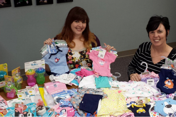 Women sitting at table covered in baby items