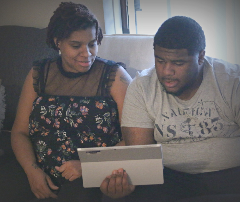 Myka and her husband Nick review information on a tablet.