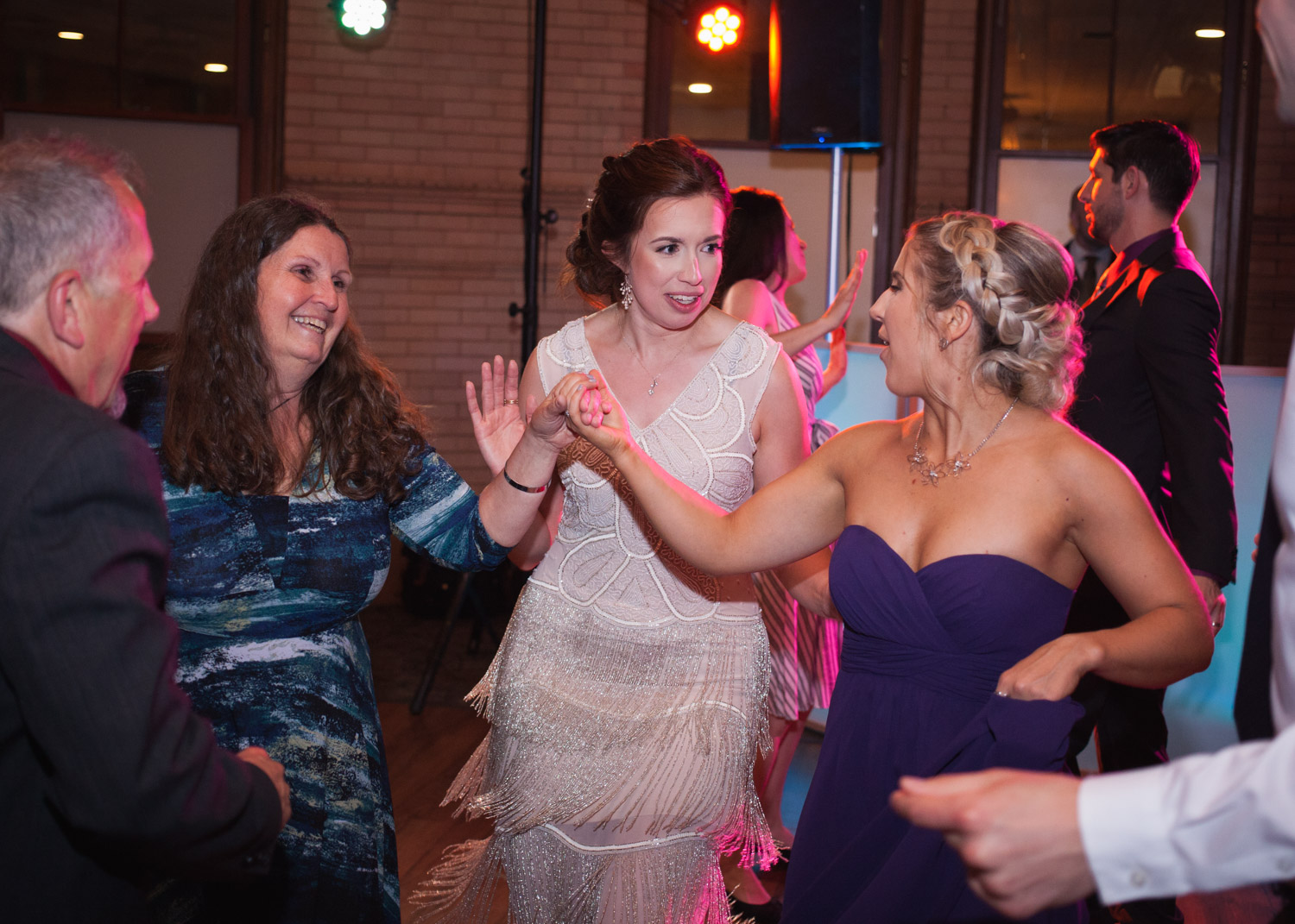 Bride in white fringe flapper dress dances with wedding guests.