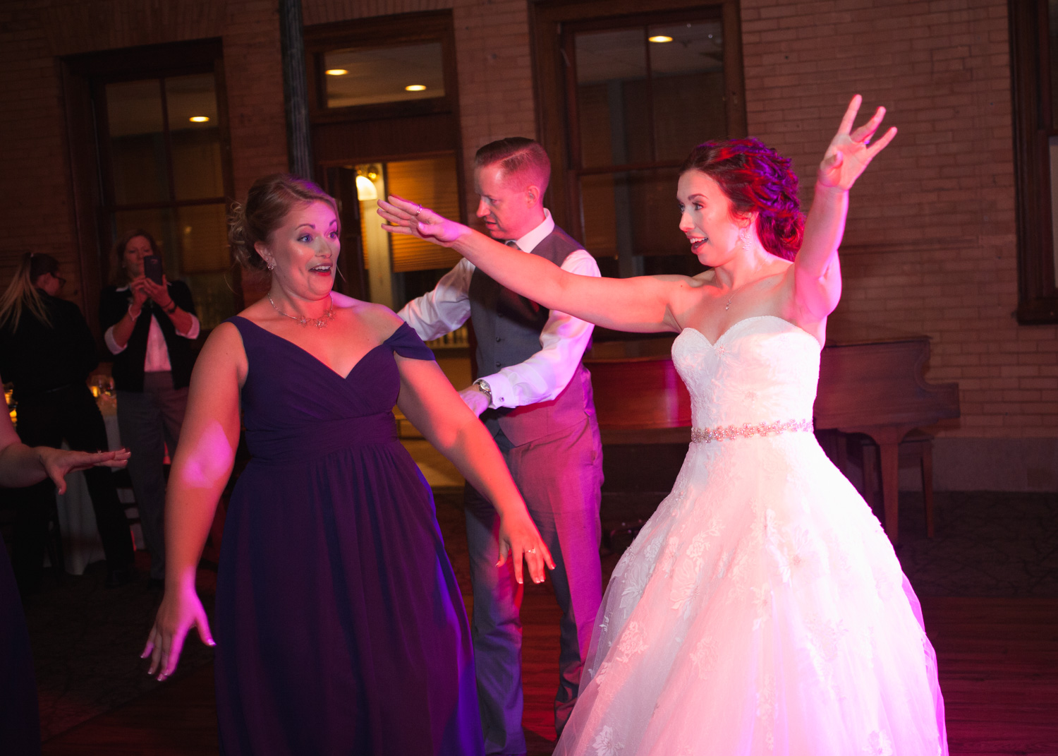 Bride in white wedding gown dances with her bridesmaid during the wedding reception at Union Station Northampton.