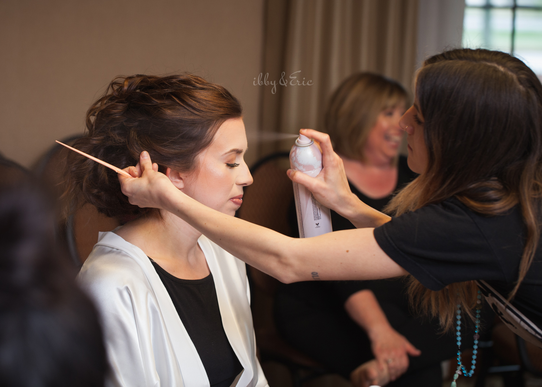 Carve Beauty Bar hair stylist applying hairspray to the bride's final look.