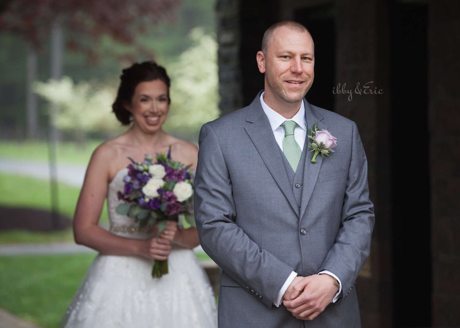 The bride smiles as she walks up behind her groom just before their first look at Stanley Park in Westfield, MA.