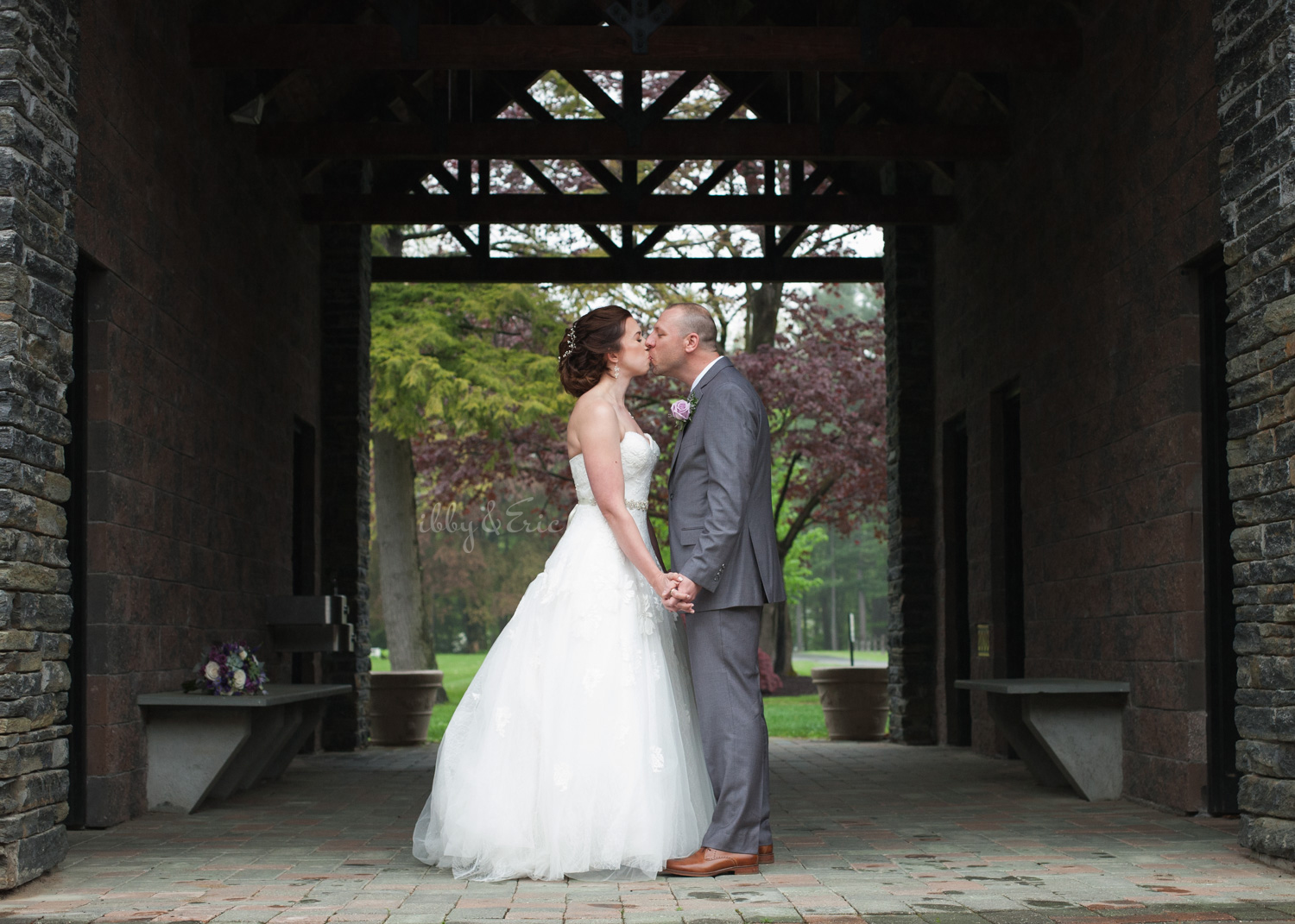 Bride and groom hold hands and kiss in a covered building on a rainy wedding day.