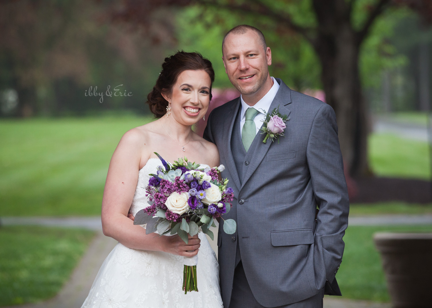 Bride holding a purple bouquet and groom smile in the garden at Stanley Park.