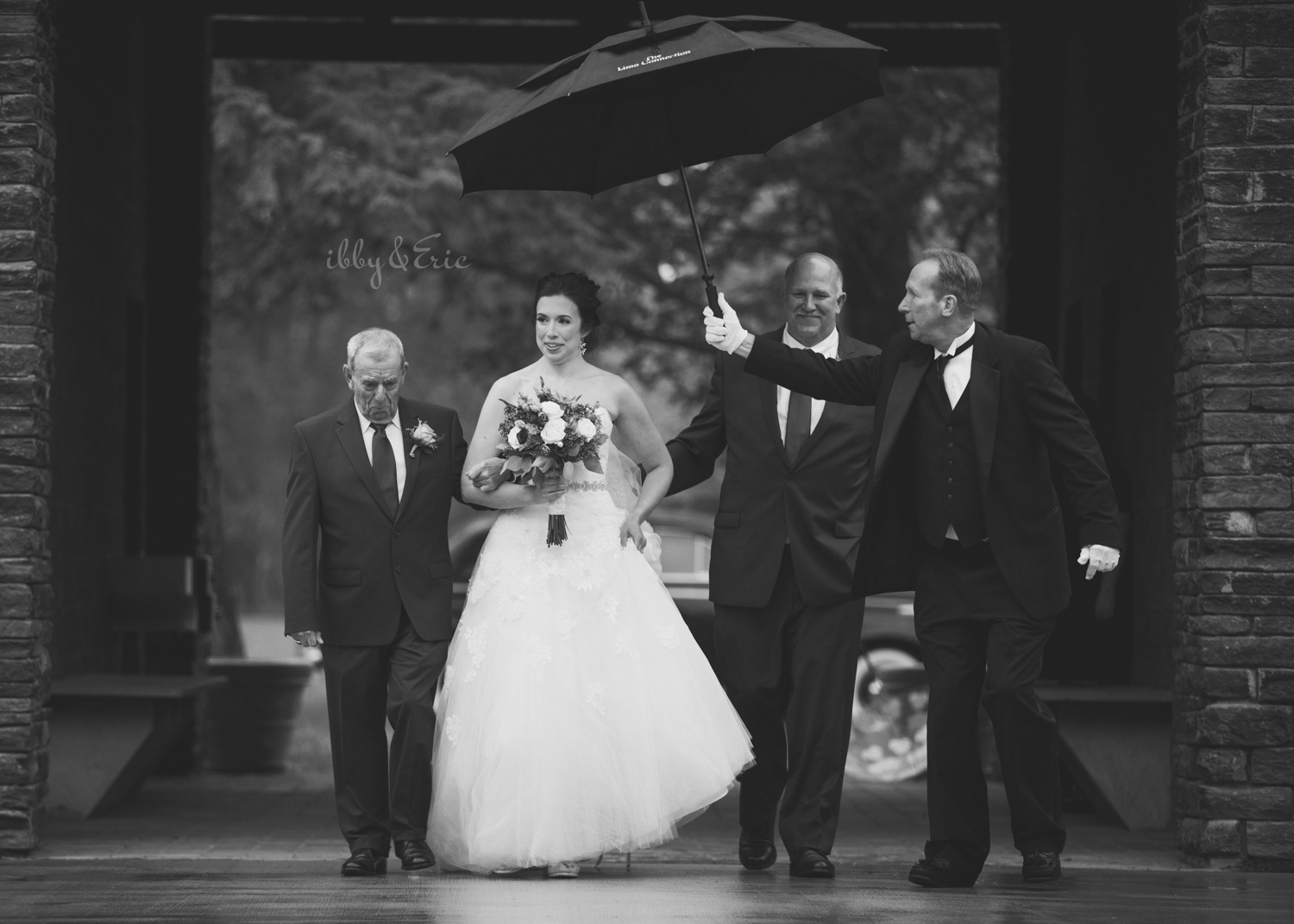 Driver holds a black umbrella over the bride, as she is escorted down the aisle by her dad and grandpa.