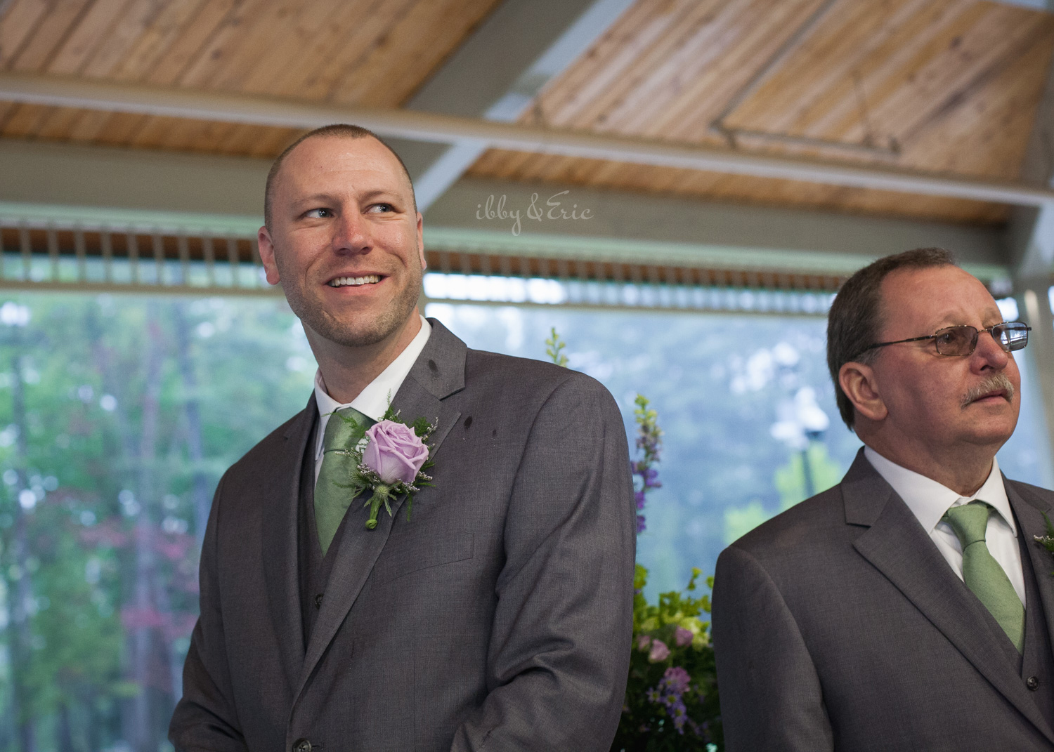 The groom wearing a gray suit and green tie smiles as he sees his bride walk down the aisle.