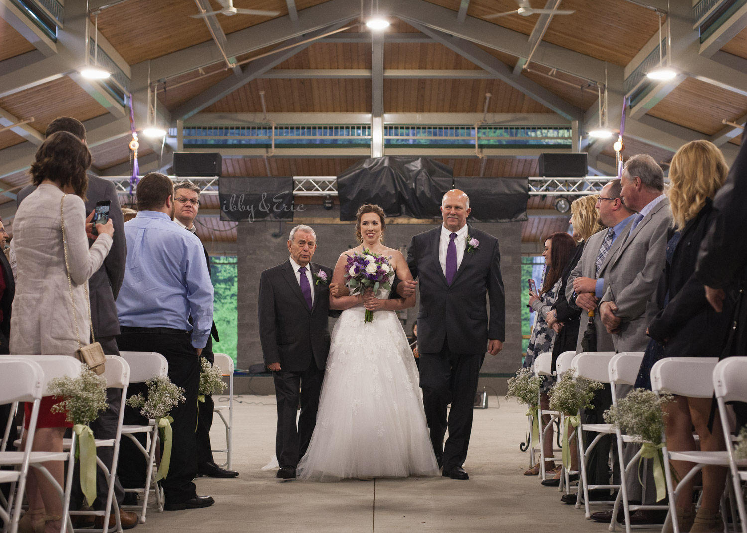 Bride with purple wedding flowers is escorted down the aisle by 2 people, her dad and grandpa.