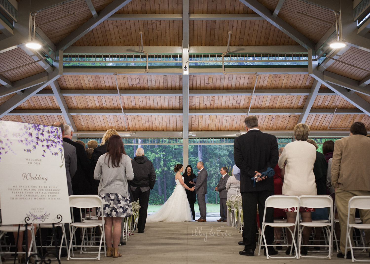 Wide angle photo of a bride and groom's wedding ceremony at the Beveridge Pavillion at Stanley Park.