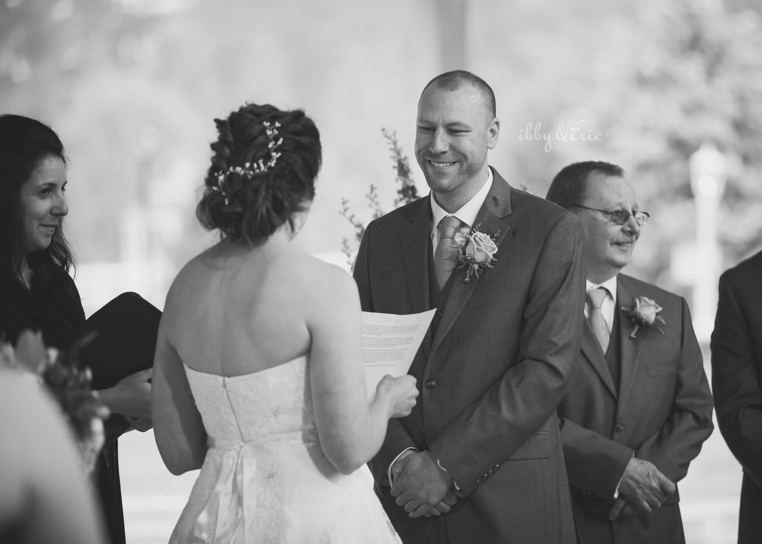 Black and white photo of the groom smiling as his wife reads her wedding vows.