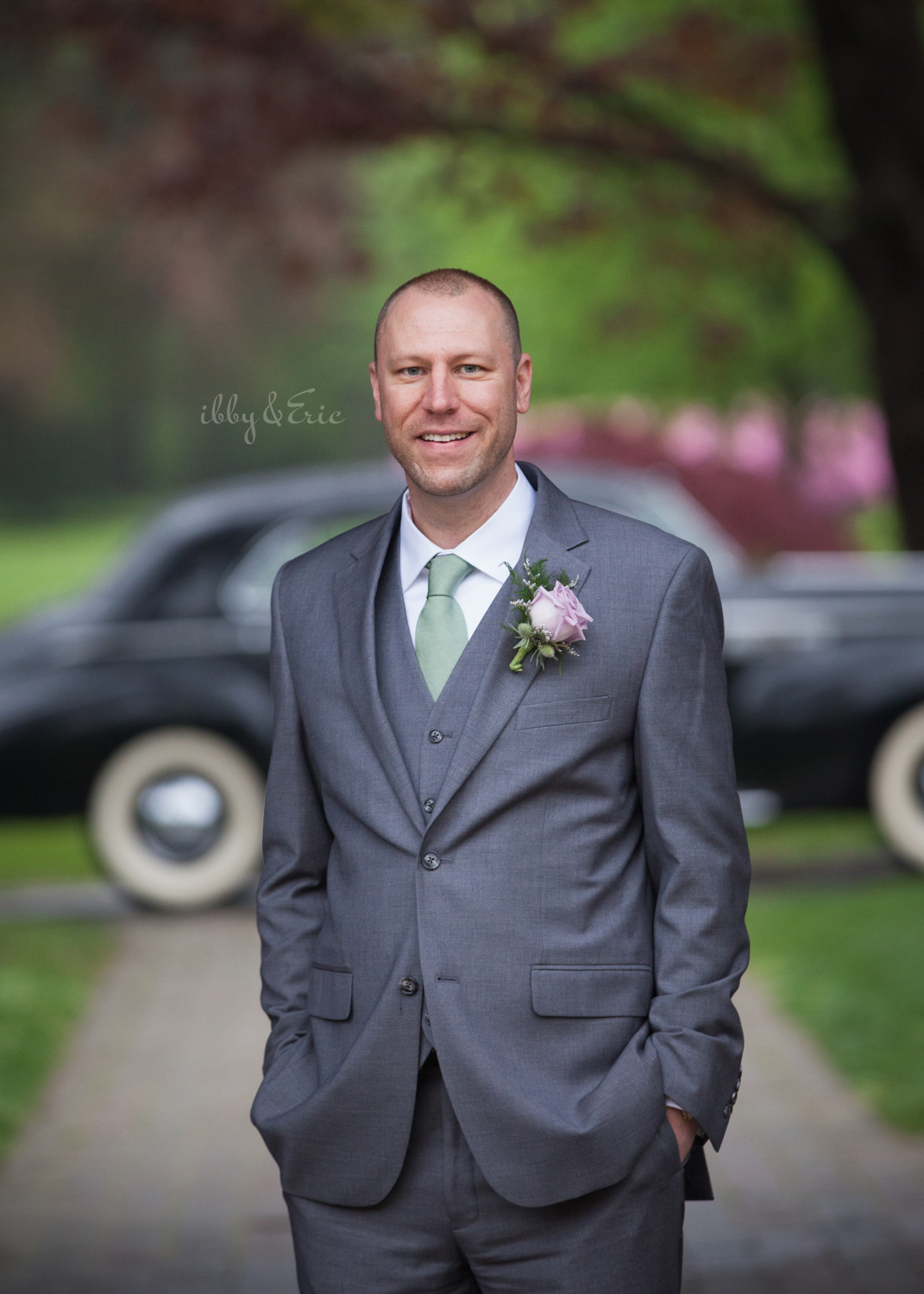 Groom in a gray suit with green tie and purple boutonniere stands with his hands in his pockets.