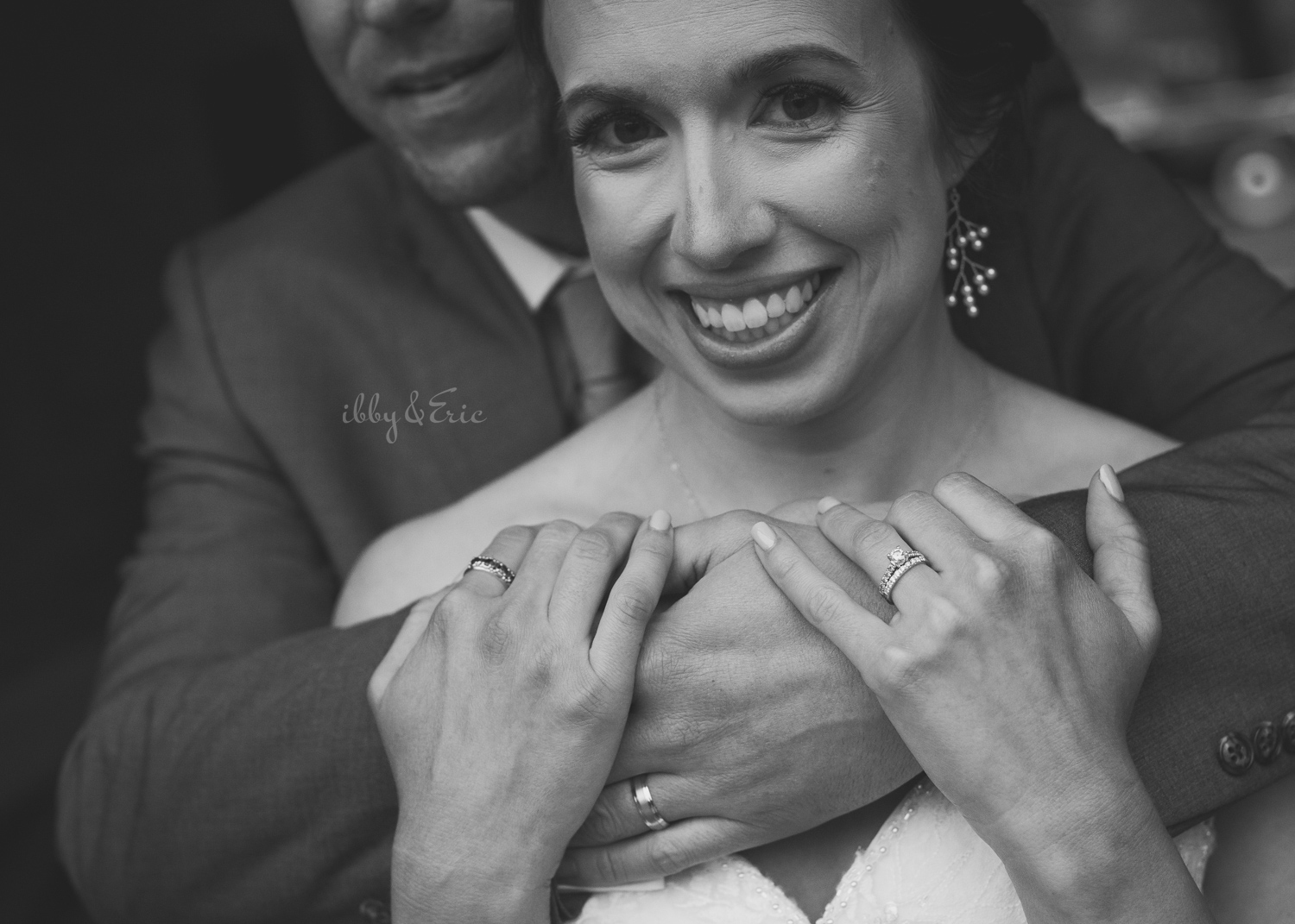 Black and white close up photo of a bride and groom's hands focusing on their wedding rings