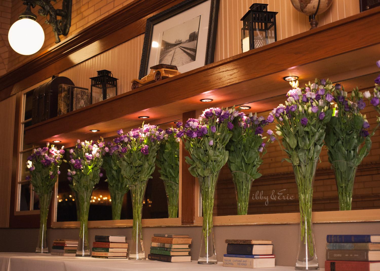 Purple floral and vintage books wedding decor