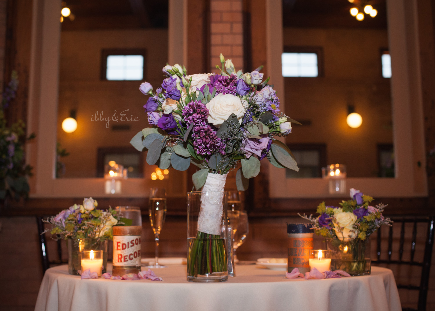 Purple wedding bouquet centerpiece with candles, Edison records, and flowers at Union Station in Northampton, MA.