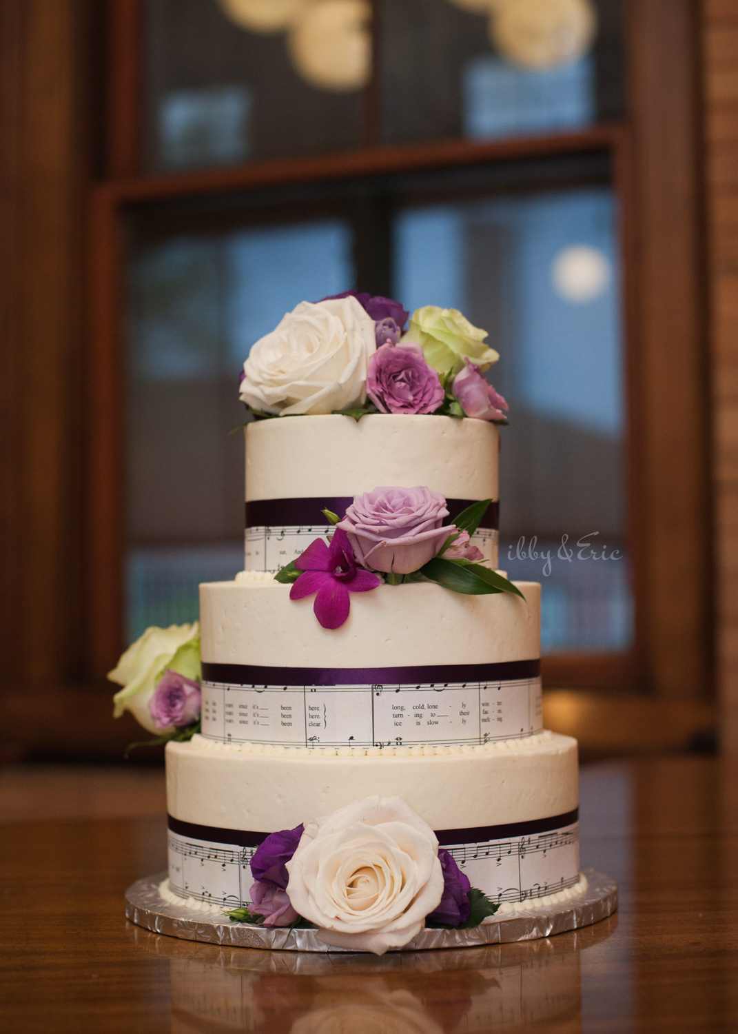 Three tier wedding cake with floral rose cake topper and sheet music wrapped around each layer.