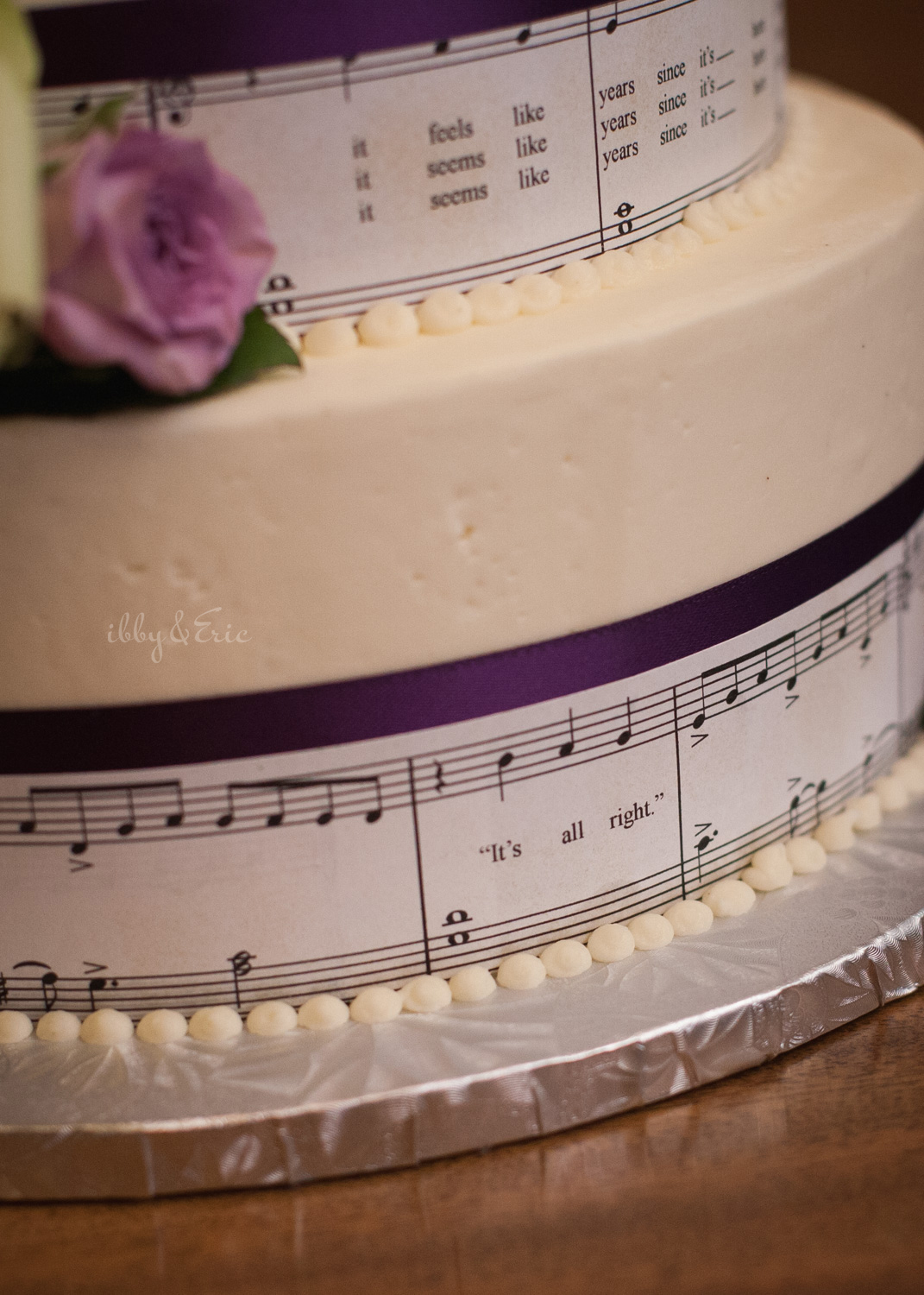 Close up of the side of a tiered wedding cake with a James Taylor sheet music band wrapped around each layer
