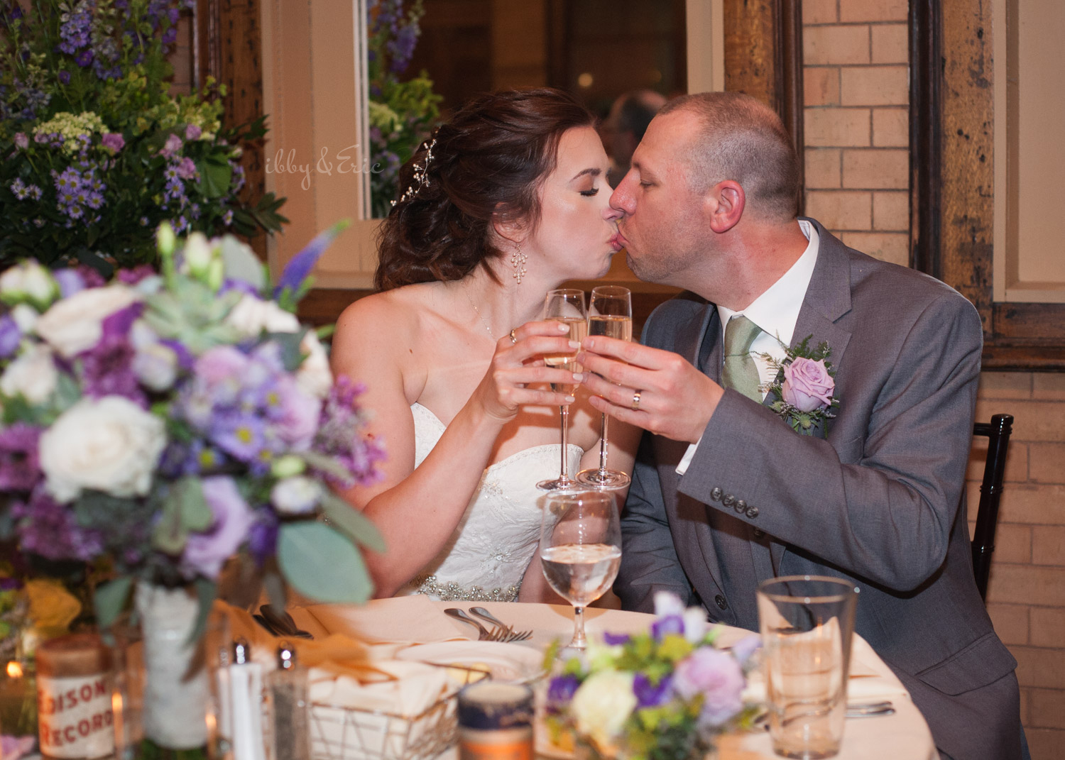 Newlywed bride and groom kiss while toasting champagne flutes