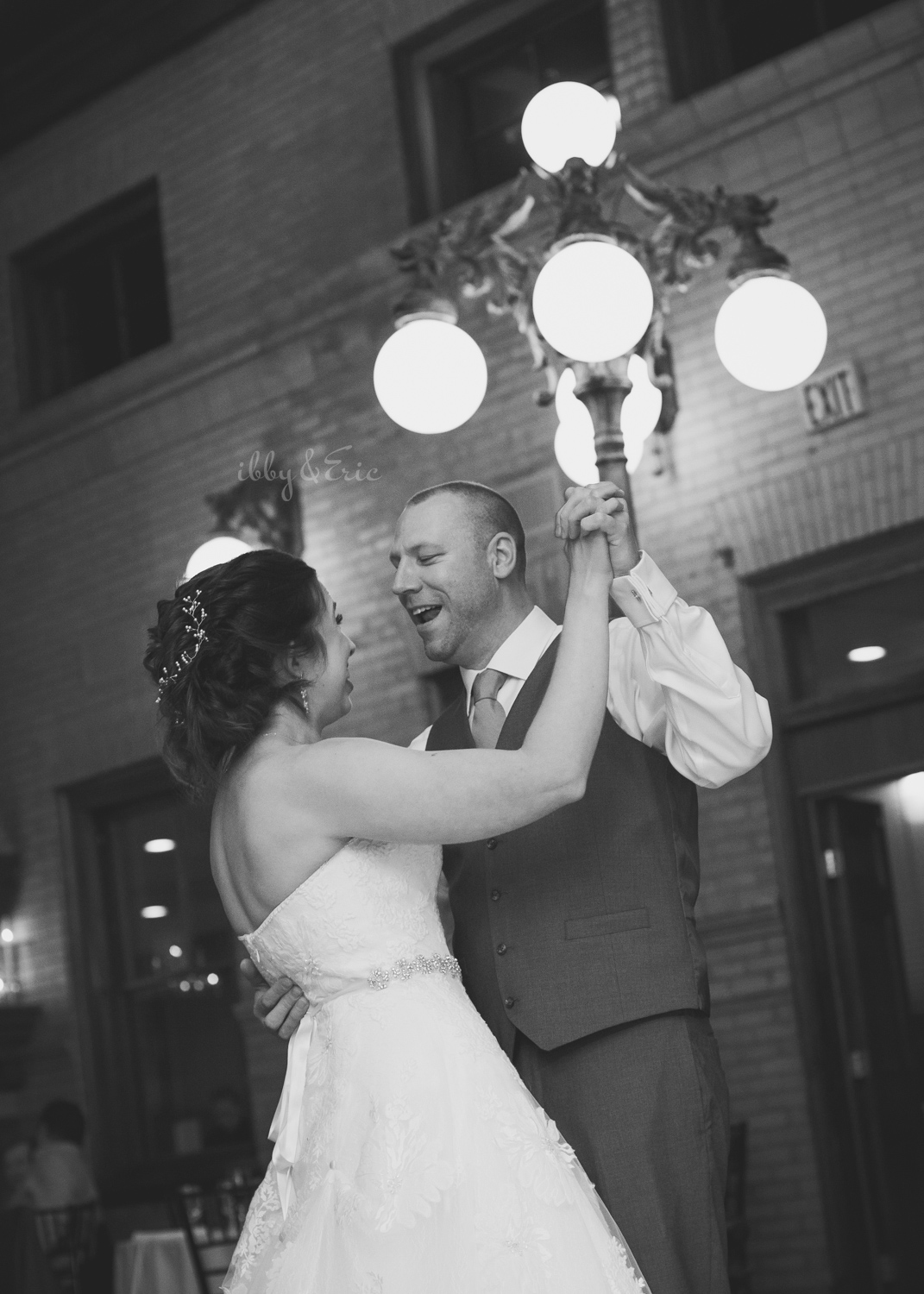 Groom sings to his wife during their first dance in front of a lamp post at Union Station Northampton.