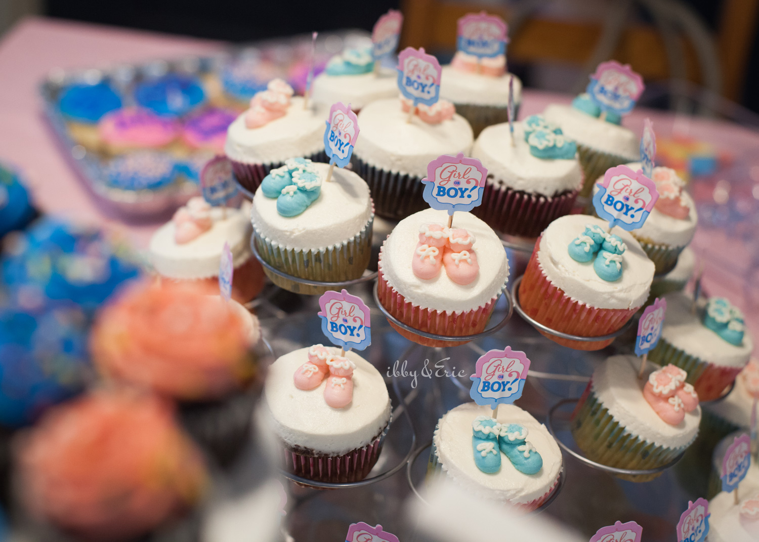 Cupcake display with pink and blue baby shoe decorations.