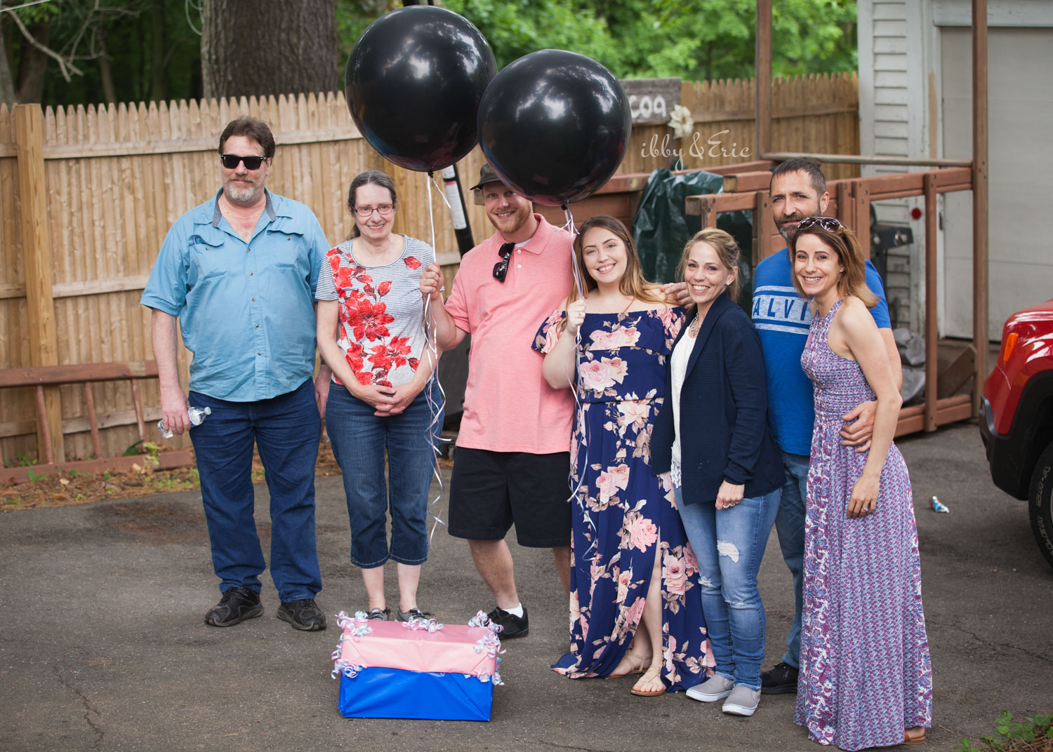 Parents to be pose for a family photo with big black balloons before revealing the gender of their baby.